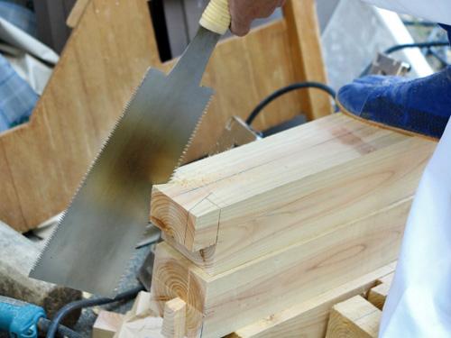 のこぎりを立てて木材を切る