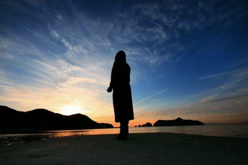 浜辺に立ち夕陽を見る女性