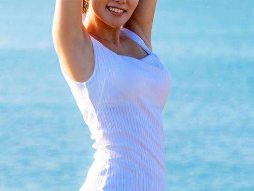 海辺で両手を上げる女性