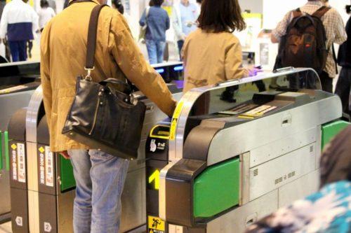 改札口を通るショルダーバッグを肩にかけたビジネスマン